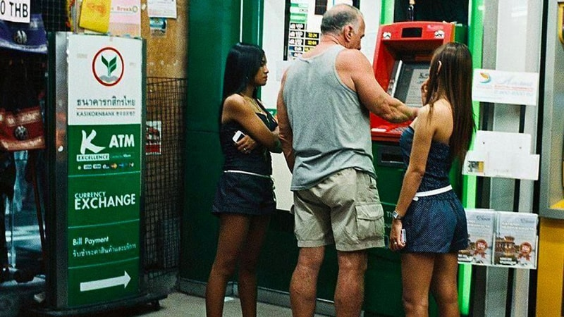 A foreigner taking money out of ATM with 2 Thai girls